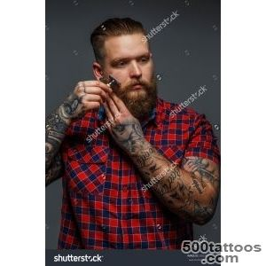 Huge Brutal Man With Tattoo Shawing His Beard With A Razor Stock _26